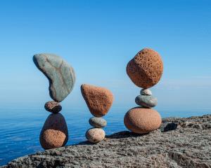 Opgestapelde stenen in balans. HSP Begeleiding helpt je meer in balans te zijn en weer terug te keren naar jezelf!
